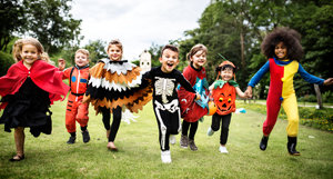 Kids in costumes running towards the camera.